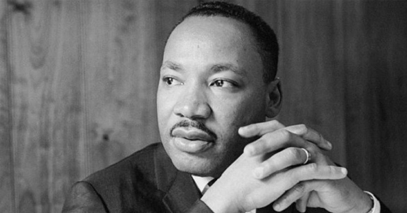 Doctor Martin Luther King Jr looking off with hands clasped
